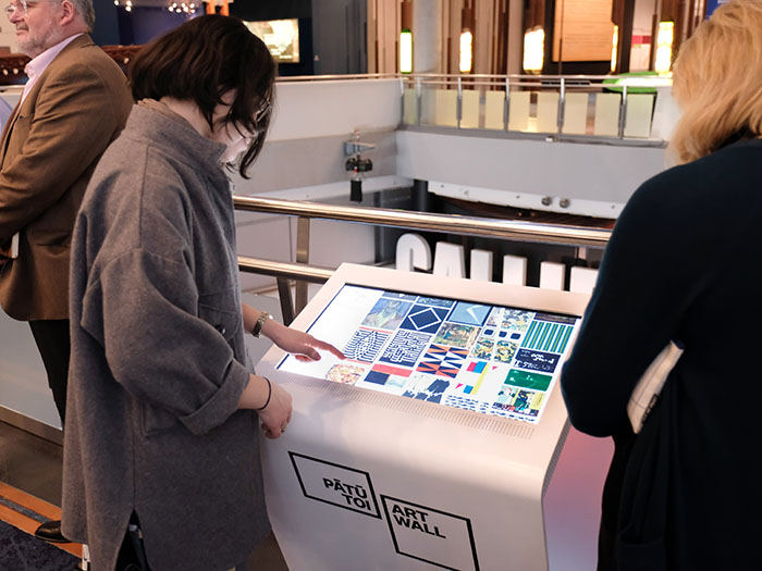 A woman uses the kiosk to browse art works to send to the wall