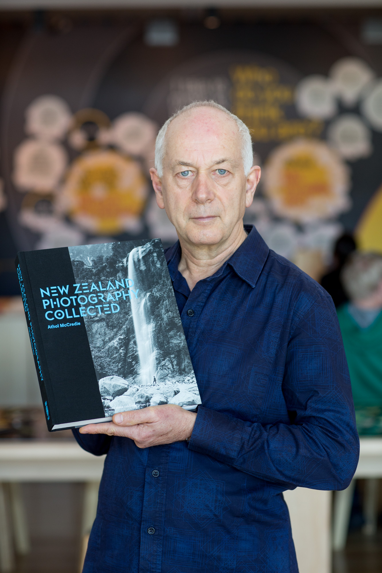 Author Athol McCredie holding a copy of his book, New Zealand Photography Collected.