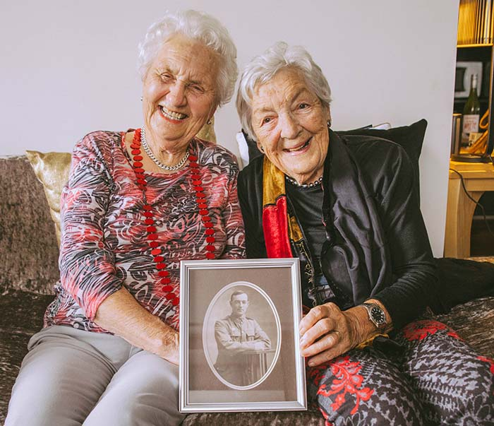 Billie and Peggy sit holding a photograph of their father who fought at Gallipoli