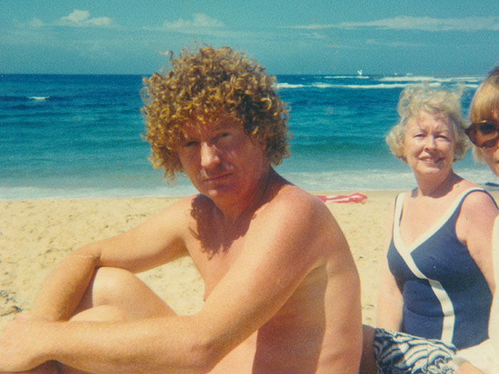 Brett Whiteley sits on a beach