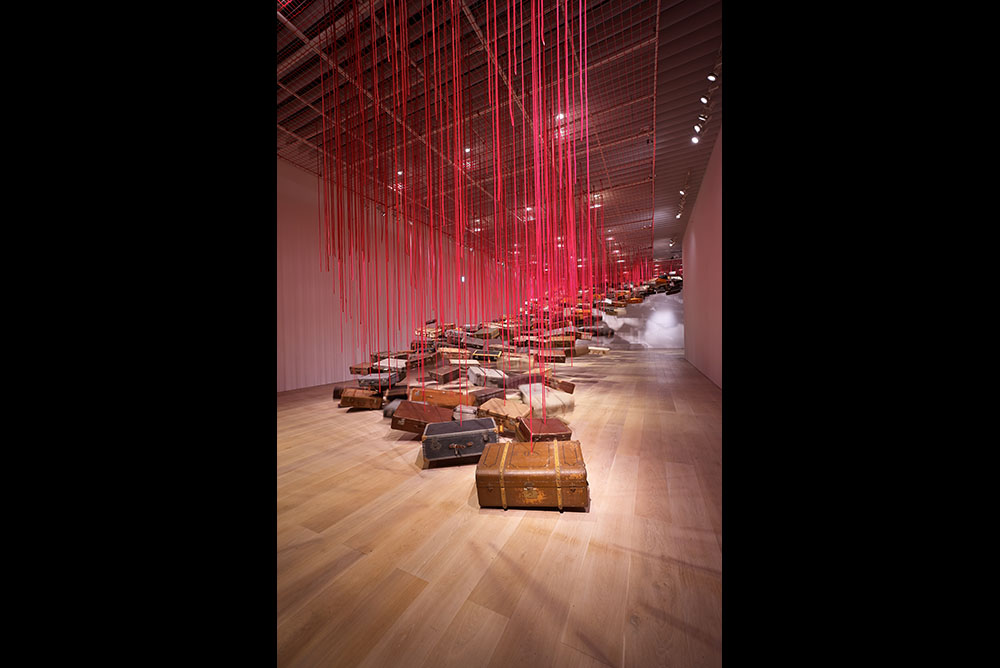 Large room with suitcases suspended from the ceiling by red thread forming a pathway to the roof