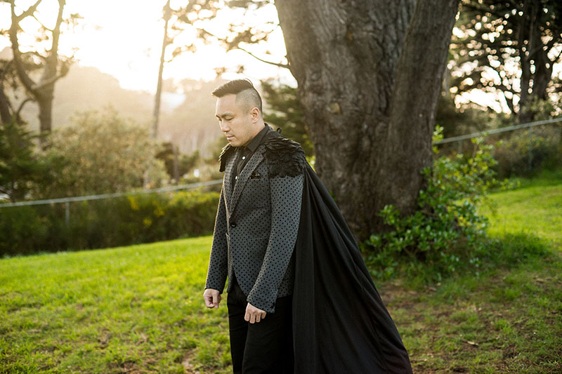 Portrait of Chris Tse wearing a jacket with a black cape and feathered shoulders