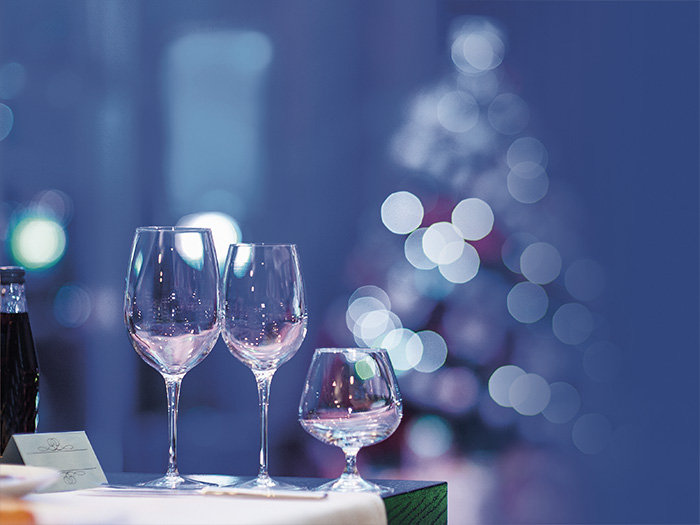 Wine glasses on a table with a Christmas tree in the background