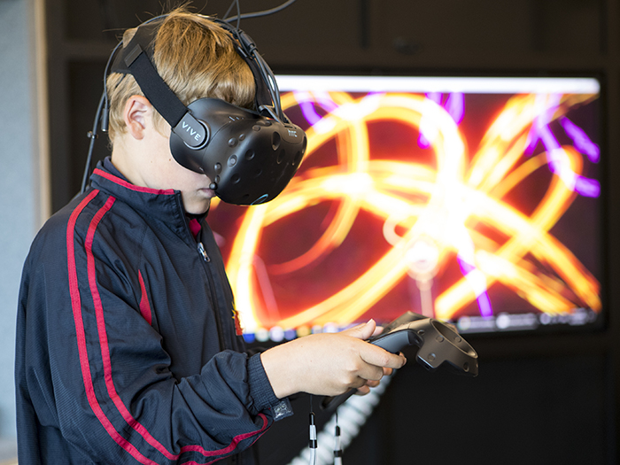 A child wear a VR headset and is creating virtual art