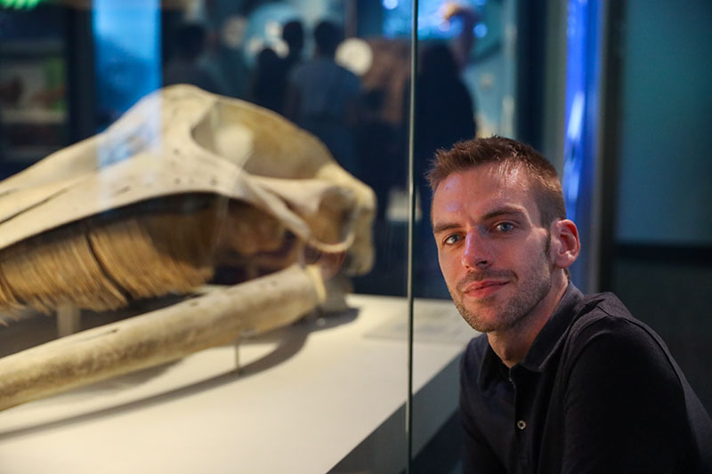 Man poses for a photo beside the skull of a whale