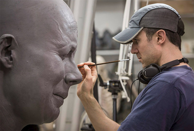 Painting one of the giant model's faces.