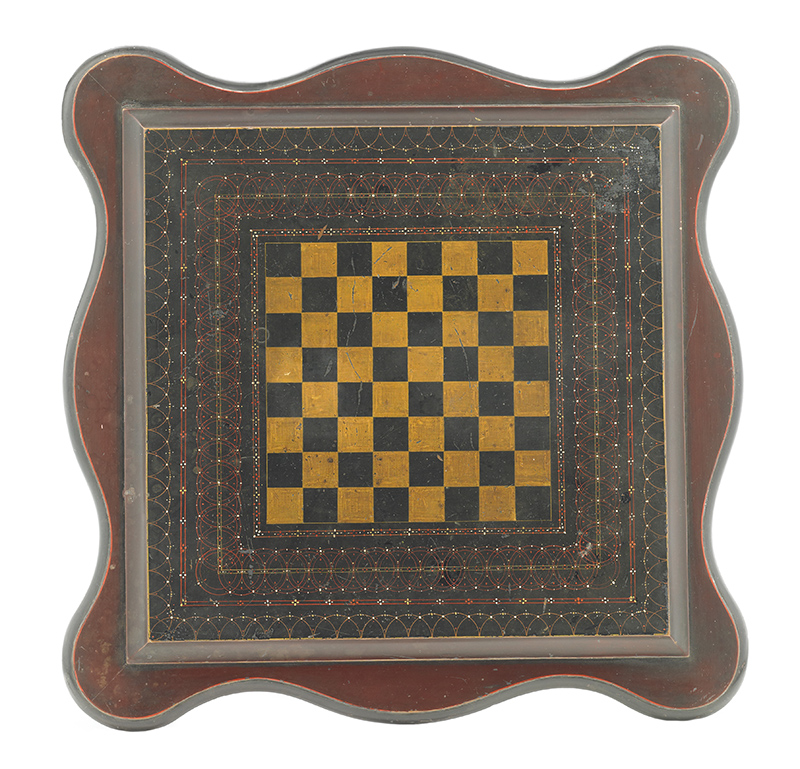 Wooden games table with a draft/chess board on top. Curved edges and an intricately painted border.