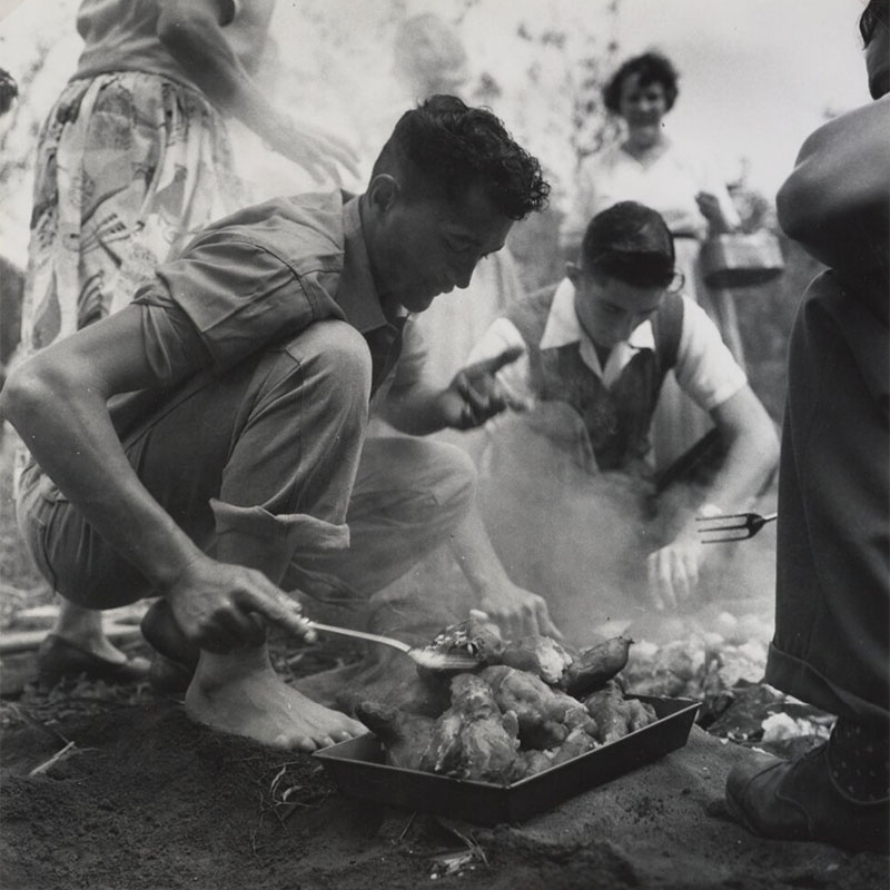 Two young men work to prepare food for a hāngī. The first is using a spatula to check on food from the hāngī while the second is lifting the food from the pit. Three women and another man are in sight around the hāngī pit.