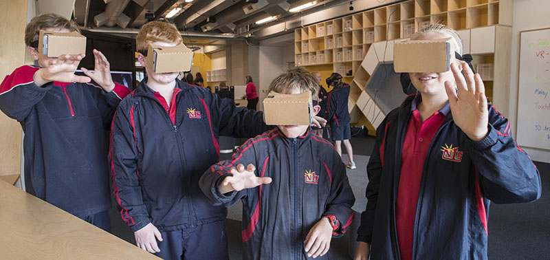 Four children wear cardboard virtual reality viewers on their faces