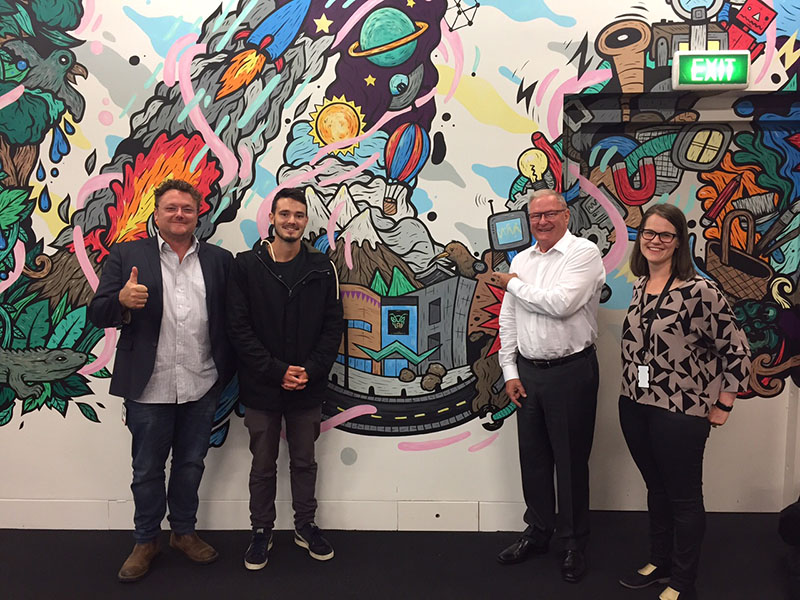 Hīnātore's Matt Richards, Gwil, Te Papa Chief Executive Rick Ellis, and Hīnātore's Miri Young in front of the wall illustration