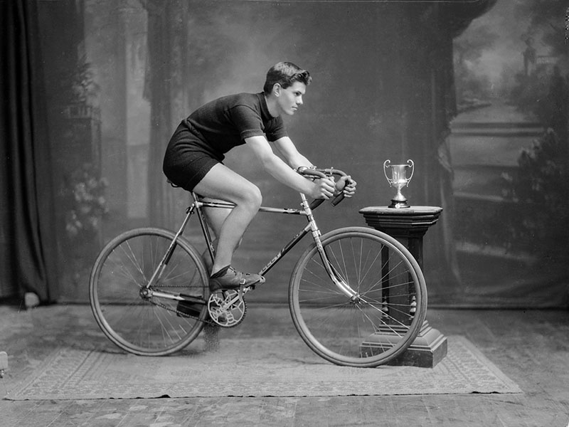 Black and white photograph of a man posing on a bicycle
