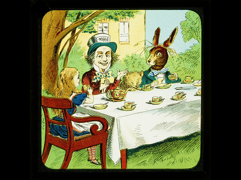 Alice, the Mad Hatter, a large rabbit, and another character sit around a table drinking from tea cups