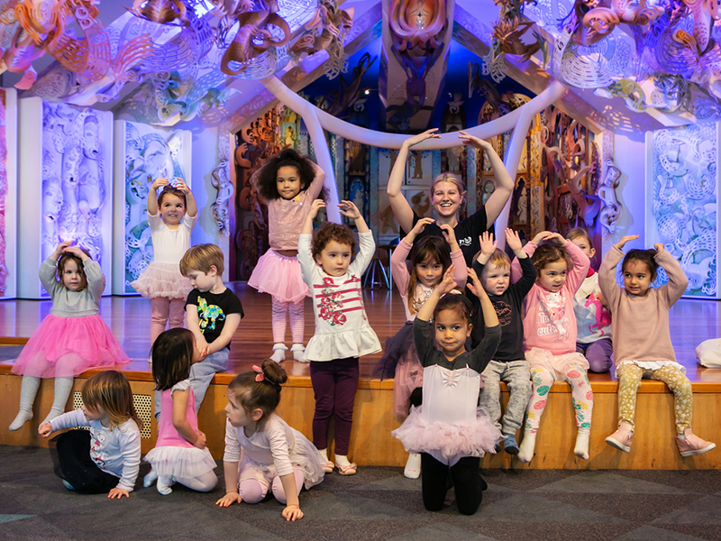 Group of young children strike a ballet pose for a photo with a member of the Royal New Zealand Ballet