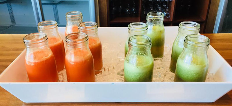 Bottles of orange and green juice sit in a tray on a counter top