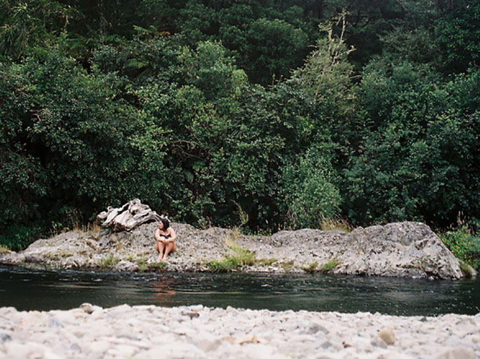 Woman sits on a riverbed