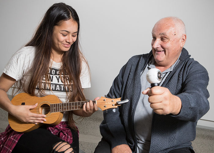 A granddaughter plays the guitar while her grandfather films with a go pro
