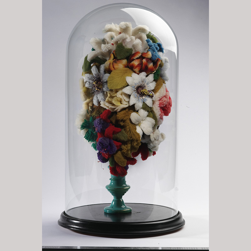 Glass dome case with bouquet of fake flowers sitting in a green vase.