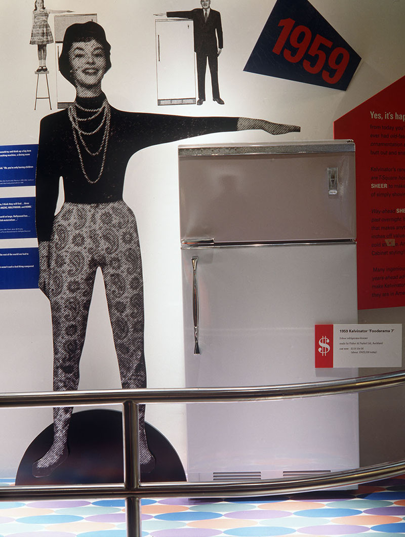 Refrigerator on display with a cardboard cutout of a woman next to it