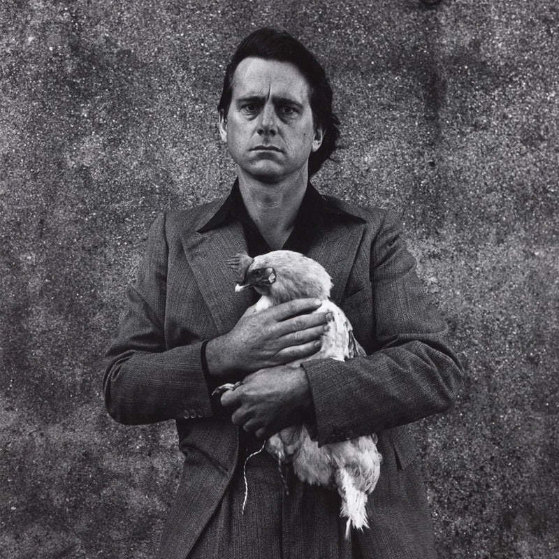 Man (Peter Peryer) wearing a jacket and black shirt holding a rooster