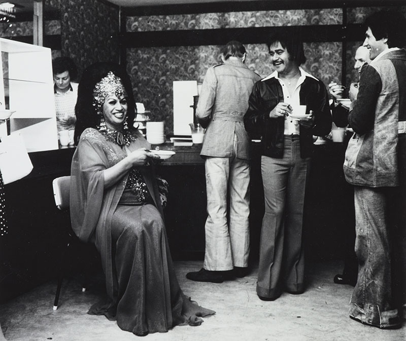 Carmen sits with a bowl while several men stand around with coffee cups and bowls in front of what appears to be self-serve breakfast