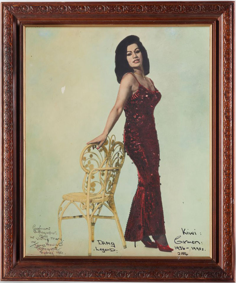 Wooden framed photo of Carmen, wearing a red sequin dress and red high heels, standing against a patio chair