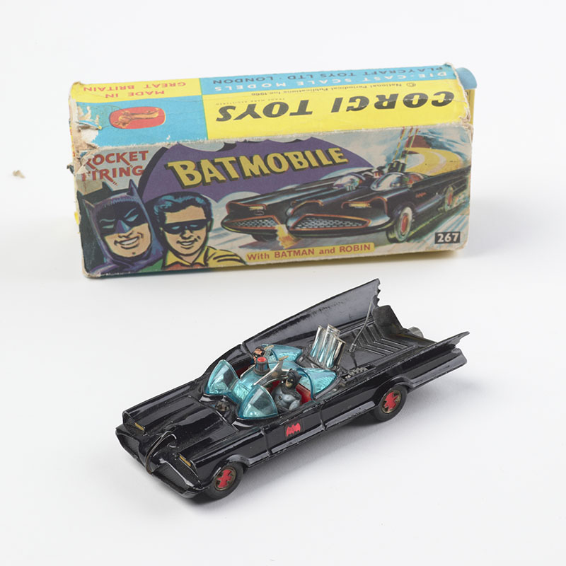 Photograph of a toy Batmobile. Behind it sits the box it came in
