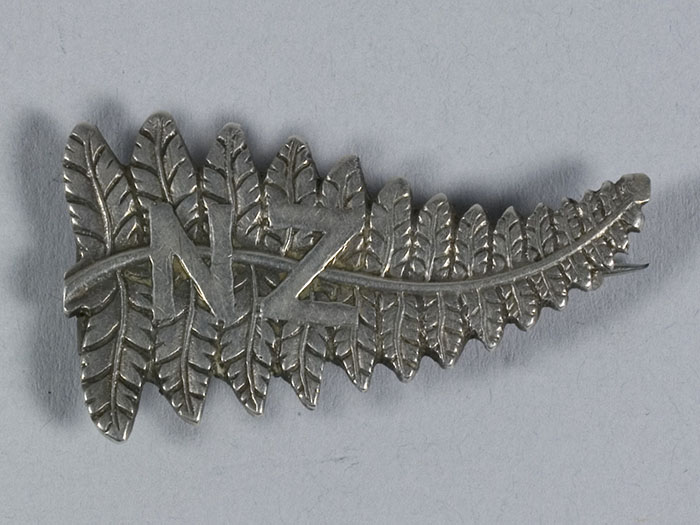 Brooch in the shape of a silver fern with the letters N and Z on it
