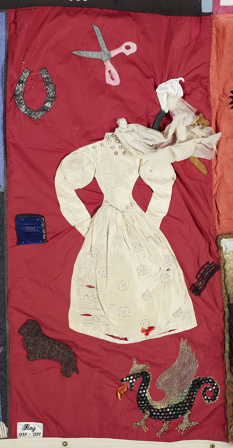 A panel from the NZ Aids Memorial Quilt. It is red with a dress on it and fabric scissors and a horseshoe and dog sown in