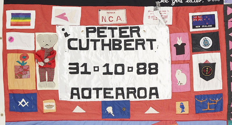 Panel of the NZ AIDS Memorial Quilt. It is predominantly red and comprises of many mini patches and the words 'Peter Cuthbert 31-10-88 Aotearoa'