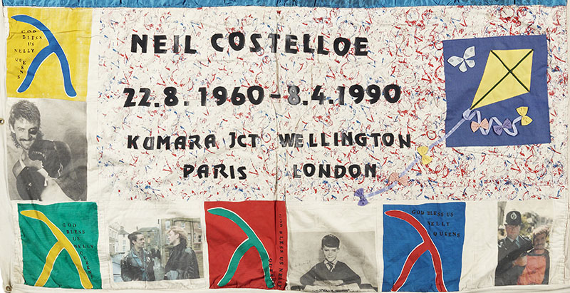A panel from the NZ Aids Memorial Quilt. It contains multiple photos as well as four signs of different colours saying 'God bless Welly queens'