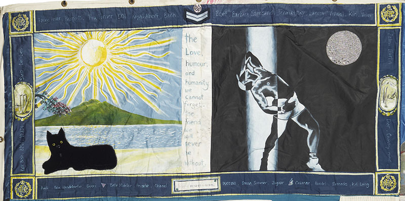 A panel from the NZ Aids Memorial Quilt. A beach scene with a black dog and a mountain in the distance, and a man posing in front of a moon. In the middle are the words 'The love, humour, and humanity we cannot forget. The friend we will never be without'