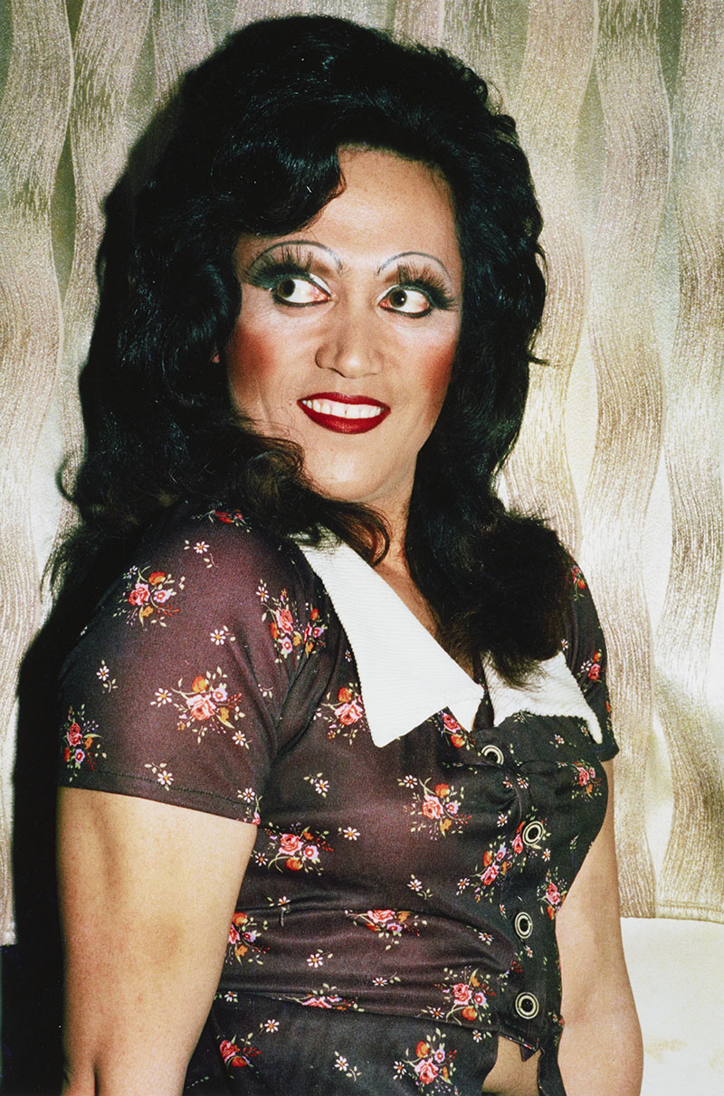 Man in drag wears a dark-coloured dress, with white collar, decorated with small floral bouquets