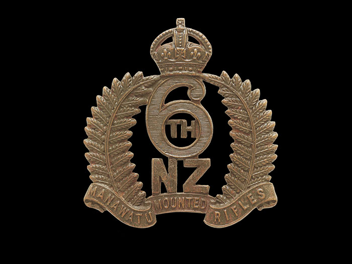 Cap badge featuring a wreath of two silver ferns, a crown, and the words 6th NZ Manawatu Mounted Rifles
