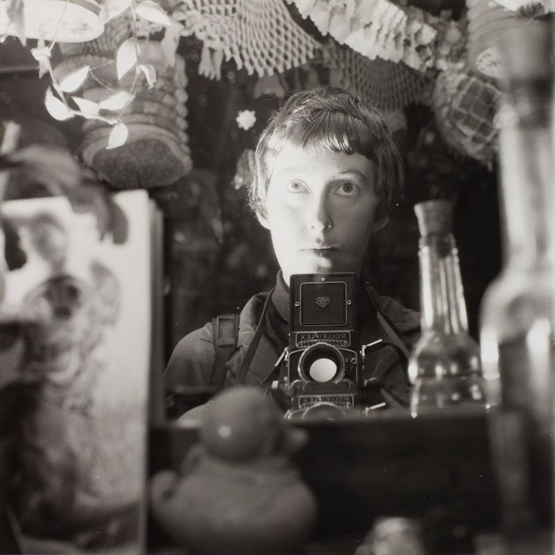 Black and white photo of a woman taking a photo of herself in the mirror with a Rolleiflex box camera