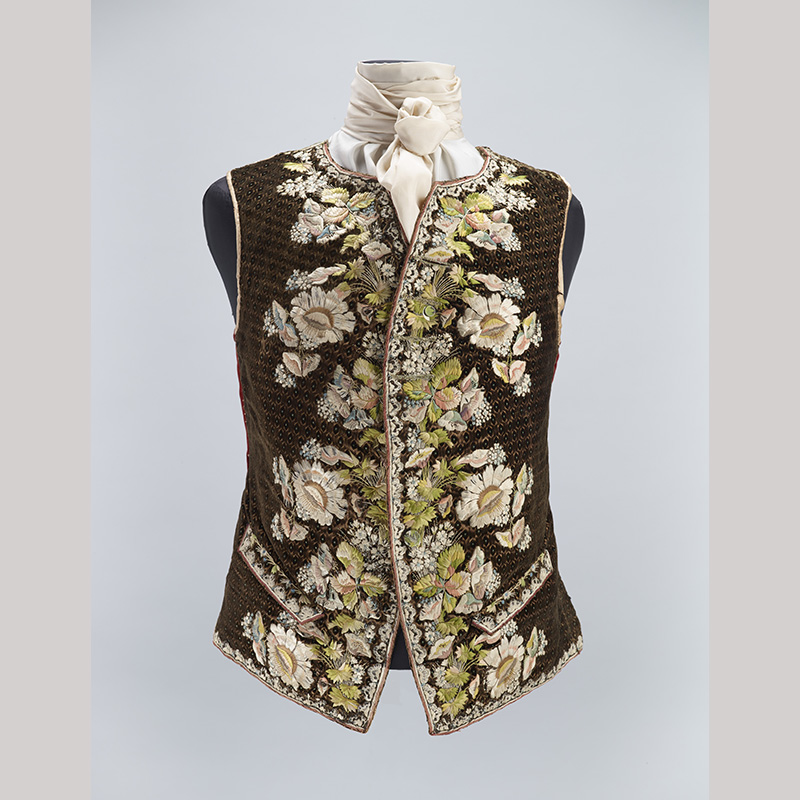 A brown tweed waistcoat on an armless mannequin with embroidered flowers on the front panels.