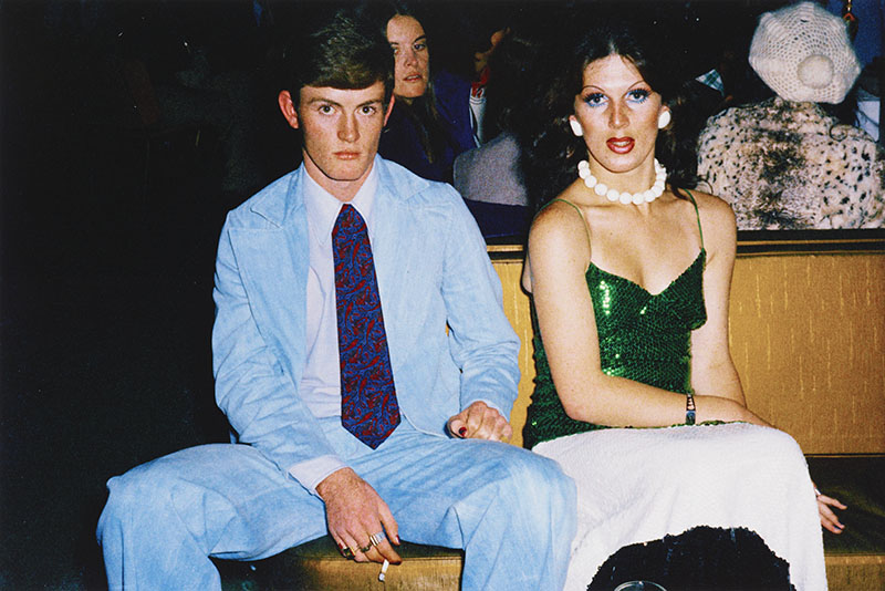 Man in light blue suit and a blue and red tie smoking a cigarette sits beside a man in drag wearing a green sequin dress and a necklace made up of large white balls
