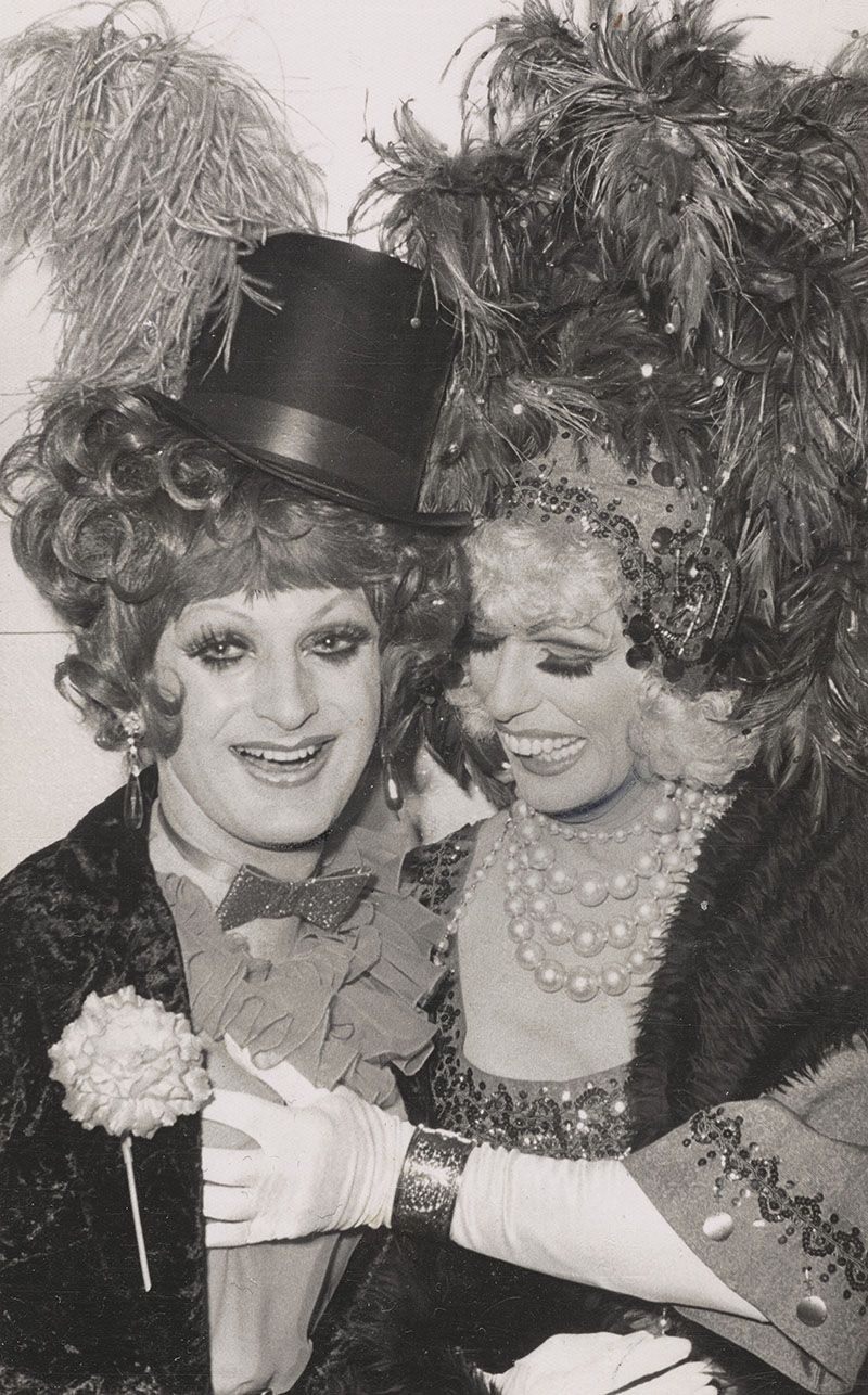 Two men dressed in drag. One wears a top hat and suit with large frilly cravat with a flower on their chest. The other is in a dress with pearls and ostrich feathers in their hair. They are touching the other person's bosom.