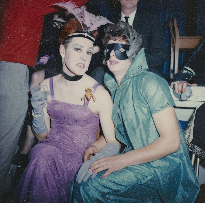 Two people pose for a photo: one in a purple dress and overall Weimar-era look, the other in a green two-piece dress and cape with black mask with feathers covering their eyes
