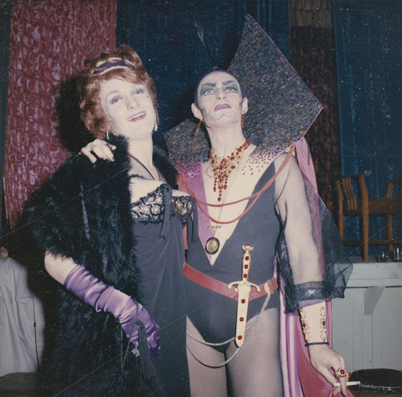 Two people are wearing elaborate costumes: one in old fashioned ball gown attire and the other in a futuristic leotard and cape ensemble