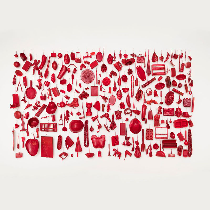 A mural of a large number of objects, ranging from headphones to an egg beater, dipped in red wax