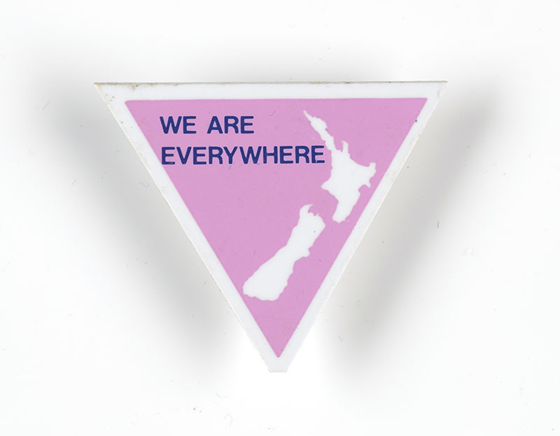 "Badge in the shape of a pink triangle with a map of New Zealand on it and the words ""We are everywhere"""