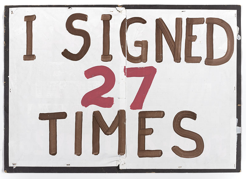 "Cardboard sign painted white with the words ""I signed 27 times"" on it"