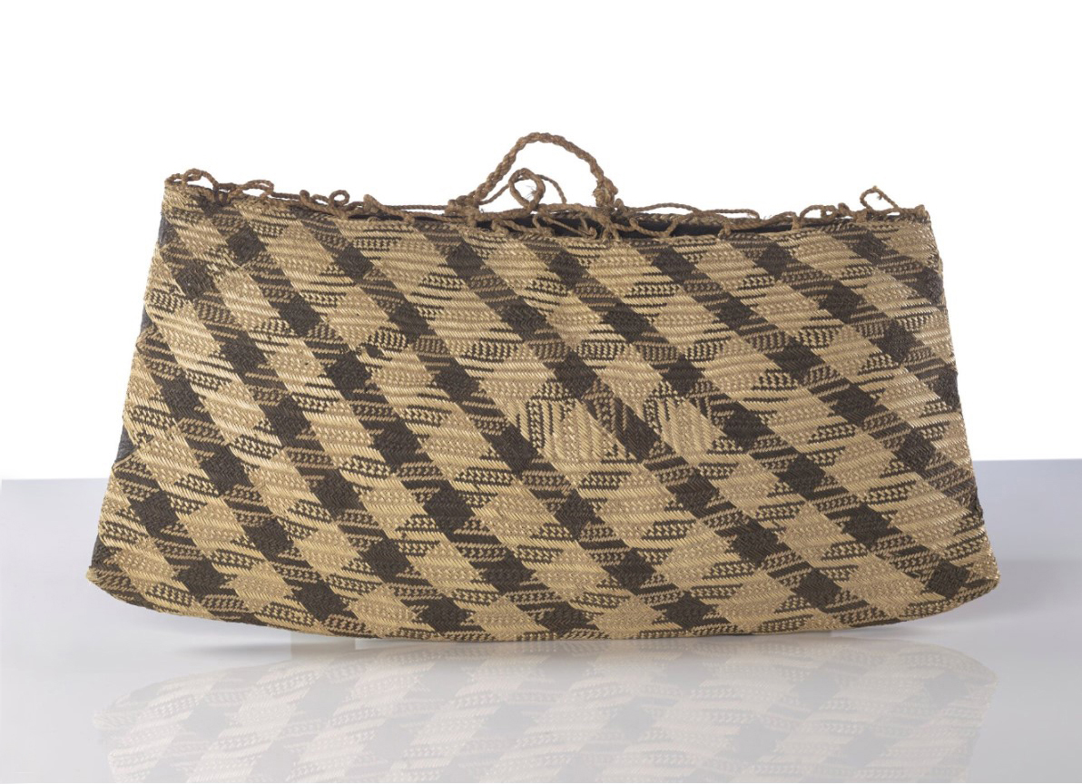 A flax bag with two handles and dark brown patterns woven into it. On a glass reflective surface and a white background.