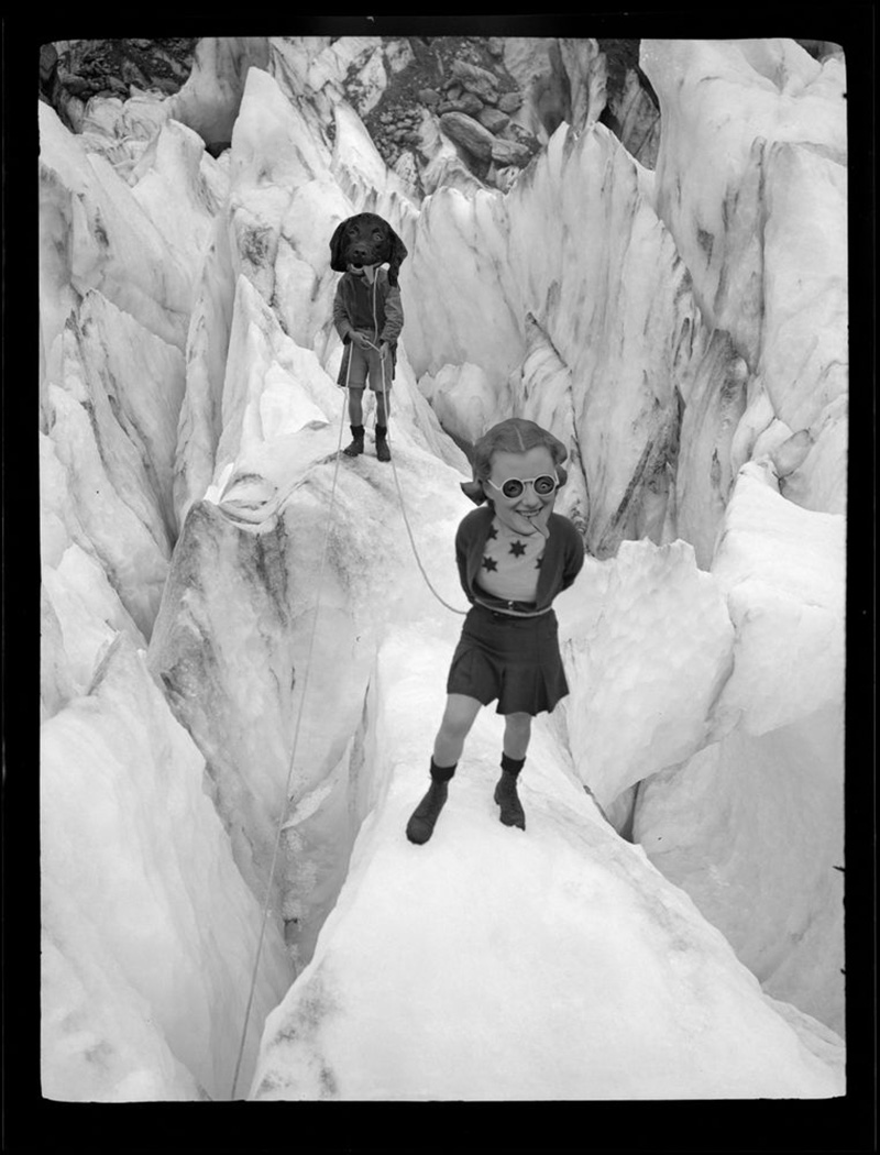 Photo montage of two people standing on an icy crevasse, one has the head of a dog with its tongue hanging out and the other has an enlarged head of a woman with the dog's tongue hanging out of her mouth. They have swapped eyes