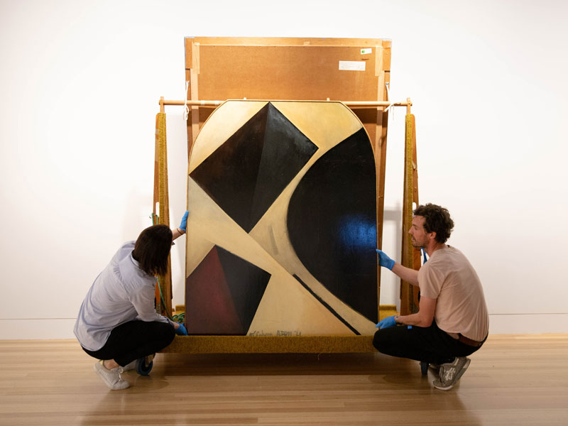 Two people install an artwork