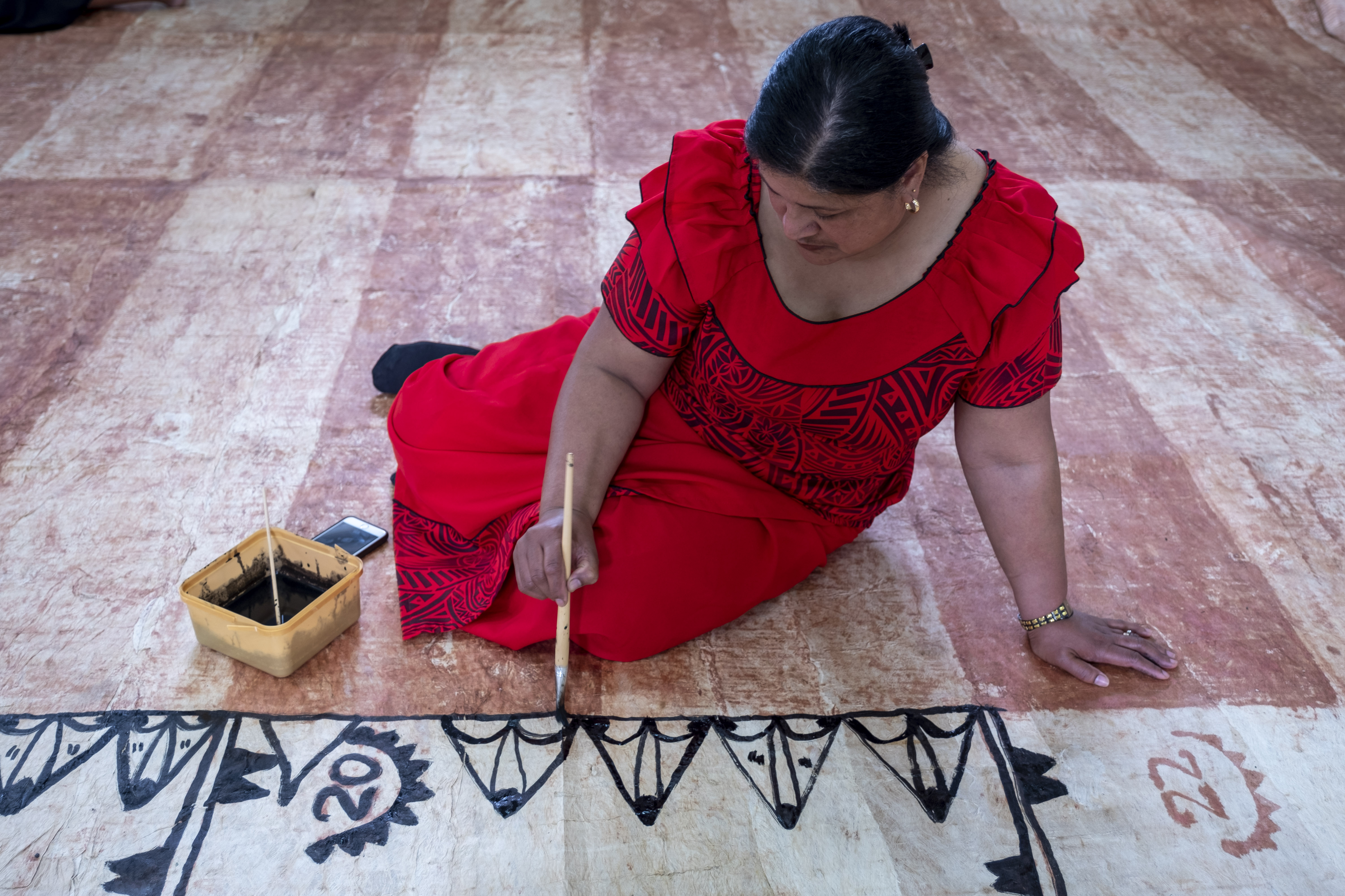 A woman in a red dress painting black ink on a tapa cloth on the floor