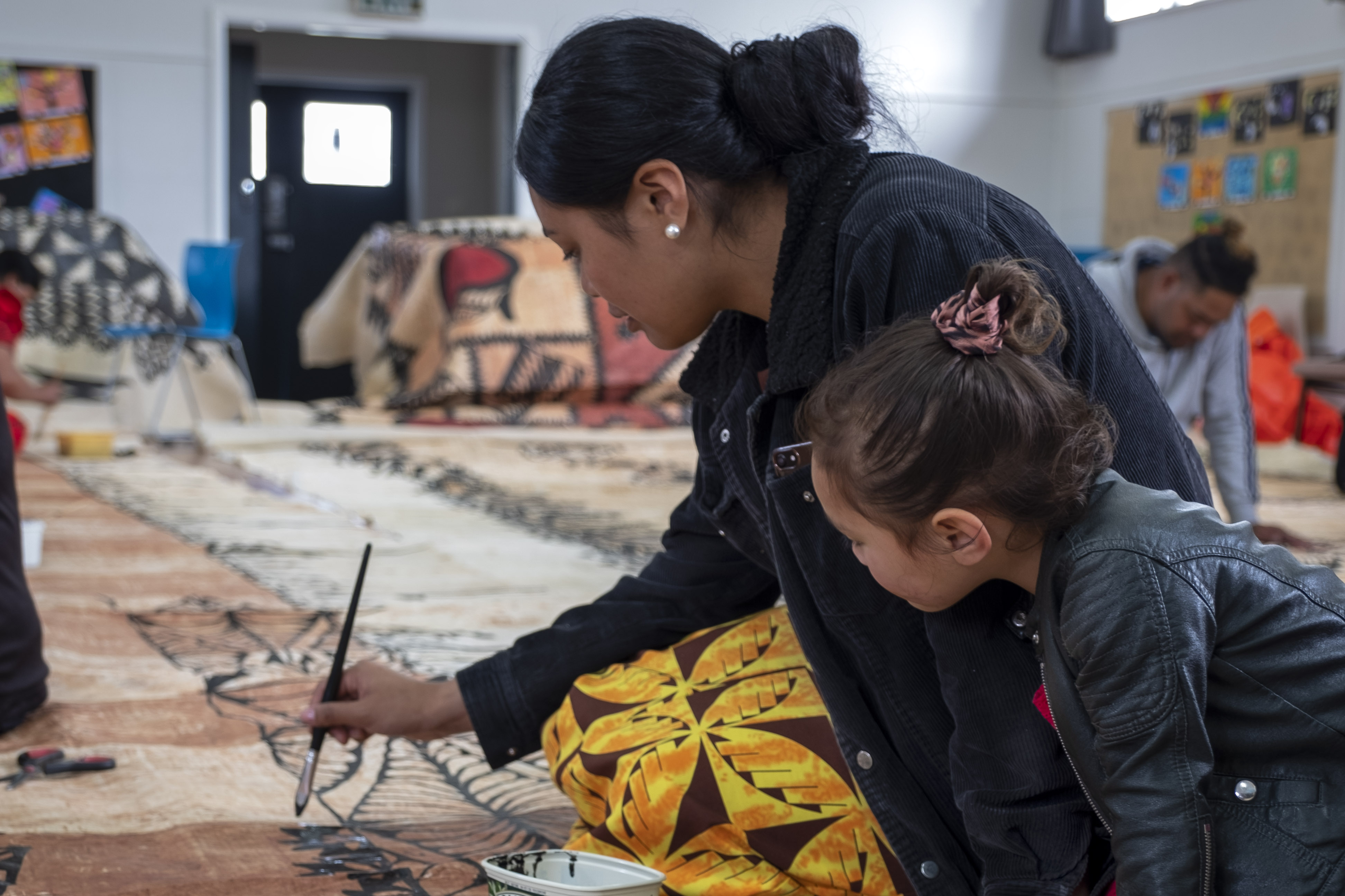 A woman painting black ink on a tapa cloth on the floor, she is being watched by a child.