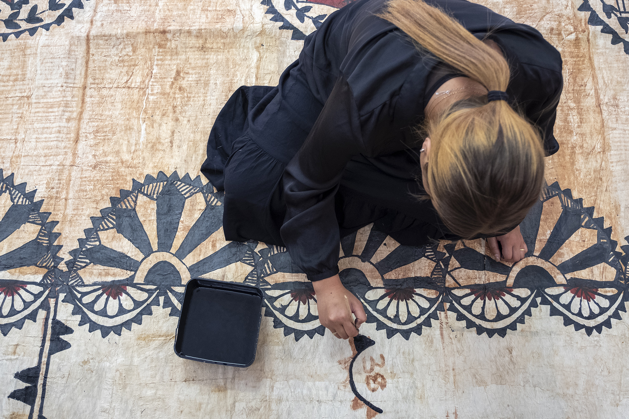 A woman painting black ink on a tapa cloth on the floor.