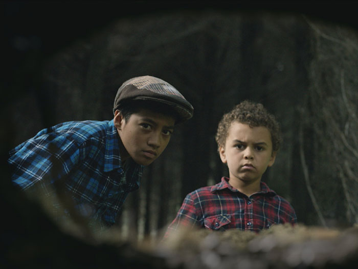 Two boys peer into a hole