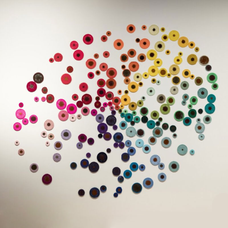 Knitted wool circles of all different colours displayed on a wall